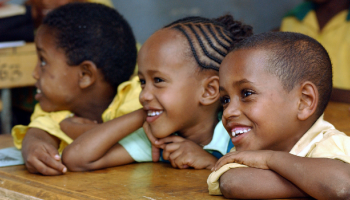 Three smiling students sitting together in a classroom. Two are girls, underlining the importance of gender equality.