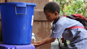 Young girl washing her hands before entering a classroom