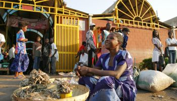Woman selling dried fish in front of a market in Zambia.