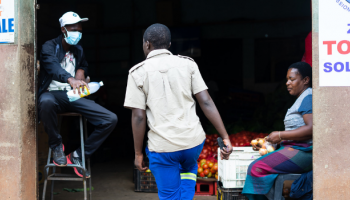 A man offers sanitizing gel to a client at a downtown vegetable market in Bulawayo, Zimbabwe.