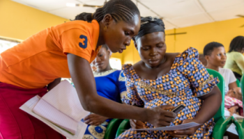 A volunteer shows a pregnant woman how to access emergency transportation to a healthcare facility on her mobile phone.