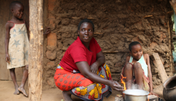 Woman cooking next to two children